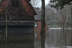 Flooding of the Falls River Pond and Stream along River Road in Essex CT on 30 March 2010. Wood, Stone and Brick Home building materials exposed to high water in this composition of Architecture to Natures revenge.