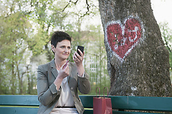 Mature woman applying lipstick for her dating in park, Bavaria, Germany