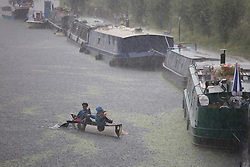 © Licensed to London News Pictures.  28/07/2021. London, UK. A group of canoeists  is caught during a torrential downpour on the canal in Hackney, east London. According to The Met Office, wet weather is expected in the capital for this week. Photo credit: Marcin Nowak/LNP