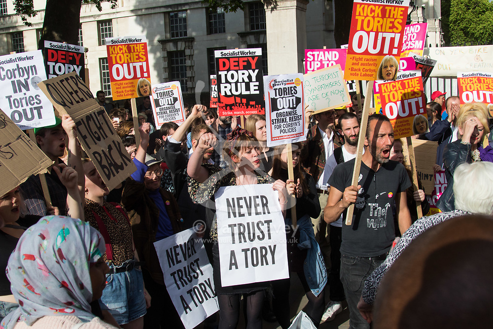 London, June 9th 2017. Anti-Tory protesters demonstrate on Whitehall outside the gates of Downing Street in London demanding embattled Prime Minister Theresa May's resignation in the wake of the general election on June 8th which saw her Conservative party lose its Parliamentary majority and seek a 'confidence and supply' deal with Northern Ireland's  Democratic Unionist Party.