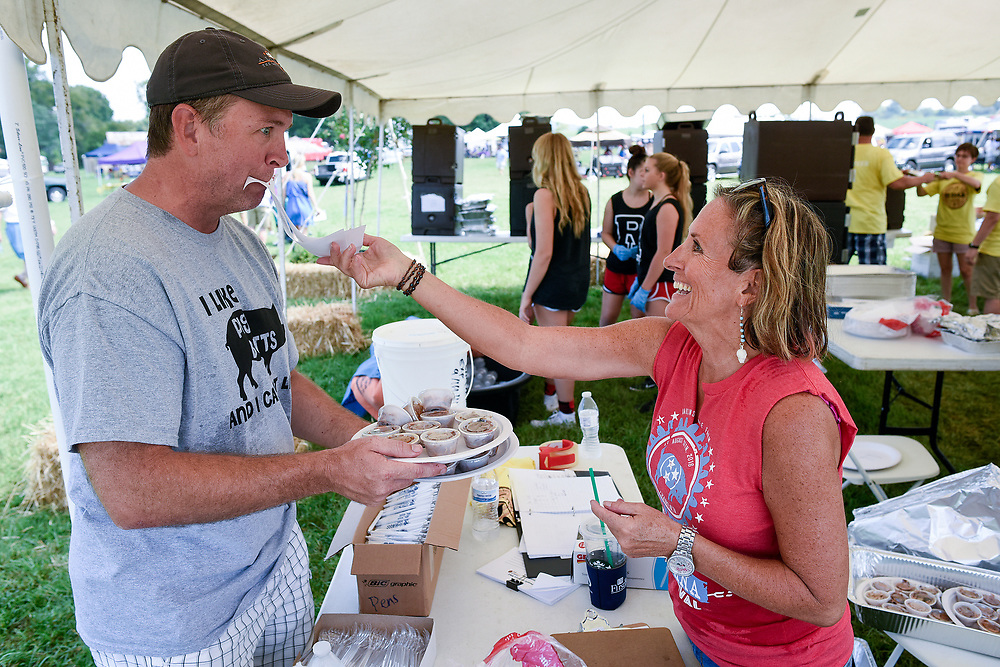 John Braswell of Brentwood has his hands full as volunteer Nancy Otte sticks a ticket in his mouth at the inaugural Great Americana Barbecue Festival at Harlinsdale Farm on August 27, 2016. The Kansas City Barbecue Society sanctions the barbecue competition, featuring 60 teams competing in five categories for over $8,000 in total cash prizes.