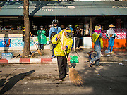 26 DECEMBER 2013 - BANGKOK, THAILAND: An anti-government protestor sweeps the street after Thai police fired tear gas at protestors at the Thai Japan Stadium. Thousands of anti-government protestors flooded into the area around the Thai Japan Stadium to try to prevent the drawing of ballot list numbers by the Election Commission, which determines the order in which candidates appear on the ballot of the Feb. 2 election. They were unable to break into the stadium and ballot list draw went as scheduled. The protestors then started throwing rocks and small explosives at police who responded with tear gas and rubber bullets. At least 20 people were hospitalized in the melee and one policeman was reportedly shot by anti-government protestors.      PHOTO BY JACK KURTZ