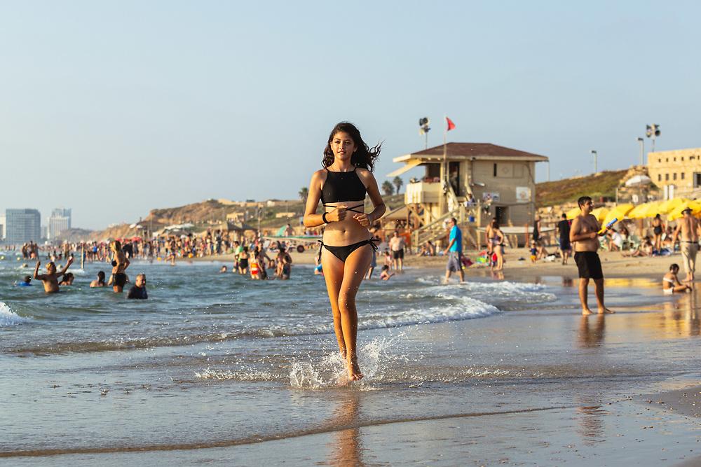 A teenager enjoys a hot summer afternoon at HaTzuk Beach (The Cliff Beach) in Tel Aviv