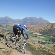 Reon Boe from Queenstown, in action during the NZBNZ South Island Downhill Cup mountain bike downhill series held on The Remarkables face with a stunning backdrop of the Wakatipu Basin. 150 riders took part in the two day event.  Queenstown, Otago, New Zealand. 9th January 2012. Photo Tim Clayton