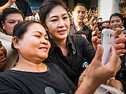 11 NOVEMBER 2016 - BANGKOK, THAILAND: YINGLUCK SHINAWATRA (center right) poses for a selfie with a supporter at a rice distribution sale in the Bangkok suburbs. Yingluck Shinawatra, the former Thai Prime Minister deposed in a coup in 2014, has started selling rice directly to Thai consumers. She buys the rice from farmers at market prices and then sells it to urban consumers at the price she paid. She said she's doing it to help out farmers, who are trying to deal with depressed prices. Yingluck is facing prosecution on corruption related charges going back to a rice price support scheme her government used to try to help farmers in 2011 and 2012. Even after the coup, she is still personally popular and hundreds of people showed up to see her at the rice distribution point at a mall in Samut Prakan province, in suburban Bangkok.   PHOTO BY JACK KURTZ