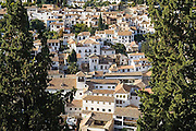 View of the whitewashed buildings and tile roofs below La Alhambra, in Granada, Andalusia, Spain.