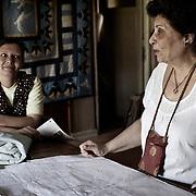 """Una voluntaria enseña el arte del patchwork a jovenes mujeres en el taller de la ONG A.P.E. en Mokattam, utilizan retales reciclados provenientes de fábricas de ropa y telas de todo Egipto. En medio del barrio de Manshiet Nasr a las afueras de El Cairo esta situado el asentamiento de Mokattam conocido como la """"Ciudad de la Basura"""" , está habitado por los Zabbaleen ,una comunidad de unos 45.000 cristianos coptos que viven desde hace varias décadas de reciclar los desperdicios que genera la capital egipcia: plástico, aluminio, papel y desechos órganicos que transforman en compost . La mayoría forman parte de la Asociación para la Protección del Ambiente (APE) una ONG que actúa en el área, cuyos objetivos son proteger el medio ambiente y aumentar el sustento de las recuperadores de basura de El Cairo. Según la ONU, el trabajo que se realiza en Mokattam como uno de los diez mejores ejemplos del mundo en el mejoramiento medioambiental. El Cairo , Egipto, Junio 2011. ( Foto : Jordi Camí )"""