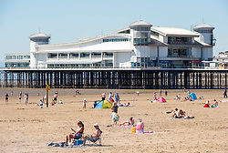 © Licensed to London News Pictures;20/05/2020; Weston-super-Mare UK. People enjoy sunny weather on the hottest day of 2020 so far on the beach and promenade at the seaside in Weston-super-Mare, on a Wednesday after some restrictions under the coronavirus lockdown are eased by the Government. People are still asked to maintain social distance to prevent the spread of the Covid-19 virus. Photo credit: Simon Chapman/LNP.