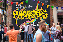 """© Licensed to London News Pictures . 25/08/2017. Manchester , UK. People on Canal Street in Manchester's """" Gay Village """" on the opening night of Manchester Pride's Big Weekend . The annual festival , which is the largest of its type in Europe , celebrates LGBT life . Photo credit: Joel Goodman/LNP"""