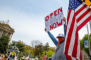 """A man holds a sign reading"""" open golf now"""" at a ReOpen PA rally in Harrisburg, Pennsylvania on April 20, 2020. Protesters gathered at the Pennsylvania Capitol to demand that Governor Tom Wolf allow businesses to reopen during the COVID-19 pandemic. (Photo by Paul Weaver)"""