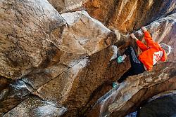 Boy climbing boulders at Hueco Tanks State Park & Historic Site, El Paso, Texas. USA.