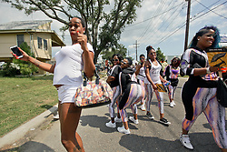 29 August 2015. Lower 9th Ward, New Orleans, Louisiana.<br /> Hurricane Katrina 10th Anniversary.<br /> A second line passes down Tennessee Street in front of Brad Pitt inspired make it Right homes as residents and mourners celebrate the lives of those lost to the storm. <br /> Photo credit©; Charlie Varley/varleypix.com.