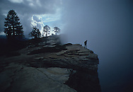"""A visitor to Taft Point peeers down into the """"fissures.""""  The spot is reached by hiking a mile from the Glacier Point Road."""