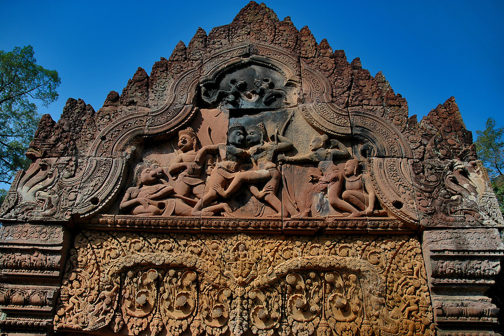 This ornamental bas-relief of a kala and warriors is from Banteay Srei, a richly decorated, late 10th century Hindu temple dedicated to Shiva located in the Angkor Wat temple complex in Siem Reap, Cambodia.<br /> <br /> The temple is built in red sandstone and has beautiful bas-reliefs and decorations. It is surrounded by three enclosures with the central structure being surrounded by a moat. <br /> <br /> Built at a time when the Khmer Empire was gaining significant power and territory, the temple was constructed by a Brahmin counselor under a powerful king, Rajendravarman and later under Jayavarman V. Banteay Srey displays some of the finest examples of classical Khmer art. The walls are densely covered with some of the most beautiful, deep and intricate carvings of any Angkorian temple. The temple's relatively small size, pink sandstone construction and ornate design give it a fairyland ambiance.<br /> <br /> This temple was discovered by French archaeologists relatively late, in 1914.