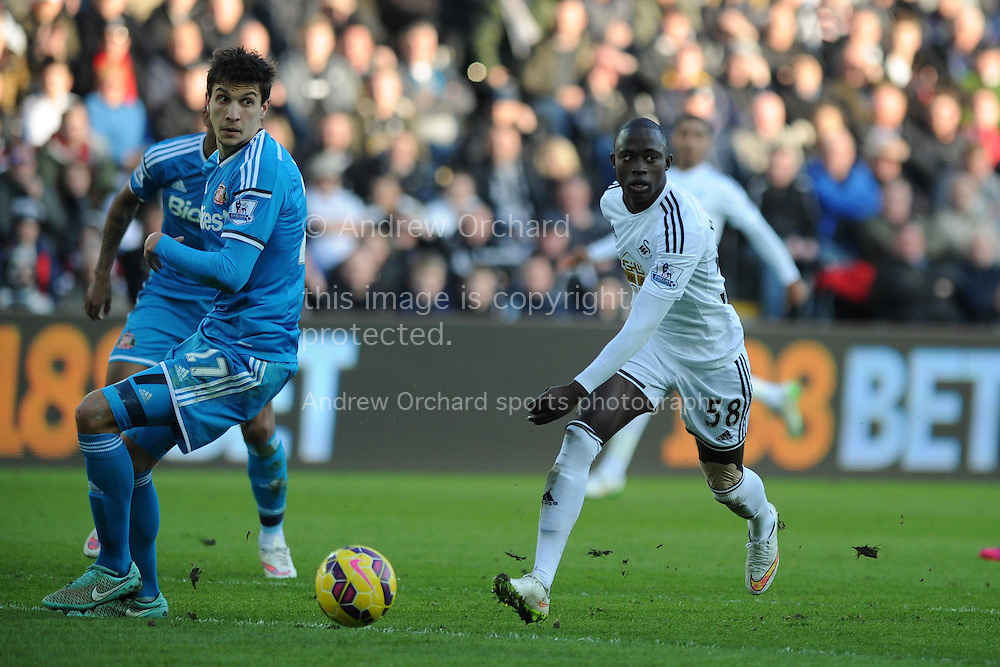 Modou Barrow of Swansea city ® goes past Sunderland's Santiago Vergini.  Barclays premier league match, Swansea city v Sunderland at the Liberty stadium in Swansea, South Wales on Saturday 7th Feb 2015.<br /> pic by Andrew Orchard, Andrew Orchard sports photography.