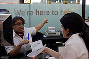 A female member of staff gives directions at the British Airways information desk in Departures at Heathrow Airport's Terminal 5