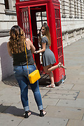Summertime in London, England, UK. Tourists in Westminster take turns to have their photo taken with one of the iconic red telephone boxes.