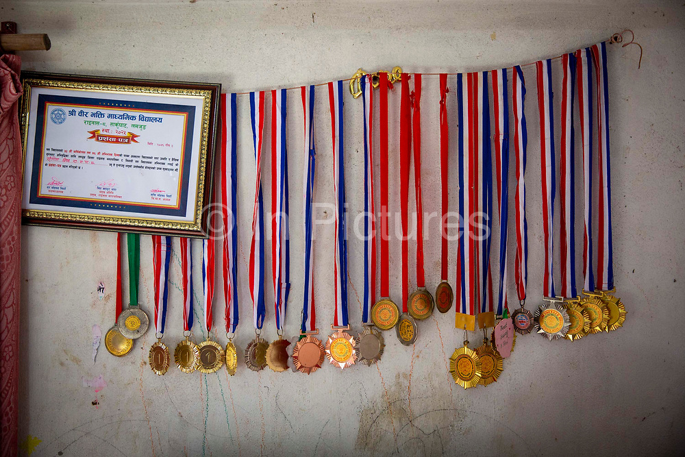 Medals and a certificate on the bedroom wall of a high achieving teenage Nepalese girl in a house on the 6th of March 2020 Lamjung District in Gandaki Pradesh, Nepal.