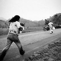 A terrified mother carrying her baby runs for cover during a firefight between FARC rebels who had been holding 40 civillians hostage at an illegal checkpoint and Governement troops who came to rescue them.<br />