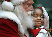 Affiong Enyenihi of Collierville, delights in a hug from Santa on Monday at Wolfchase Galleria .  It was the two-year-olds first ever visit with Santa and one she will remember.