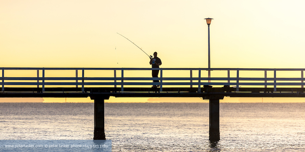An early morning silhoutte of a lone fisherman about to cast his line from the Orakei Whalf.