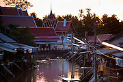 "10 JULY 2011 - AMPHAWA, SAMUT SONGKRAM, THAILAND:   Buddhist monks paddle out of Wat Amphawan Chetiyaram in Amphawa, Thailand, about 90 minutes south of Bangkok. The Thai countryside south of Bangkok is crisscrossed with canals, some large enough to accommodate small commercial boats and small barges, some barely large enough for a small canoe. People who live near the canals use them for everything from domestic water to transportation and fishing. Some, like the canals in Amphawa and nearby Damnoensaduak (also spelled Damnoen Saduak) are also relatively famous for their ""floating markets"" where vendors set up their canoes and boats as floating shops.     PHOTO BY JACK KURTZ"
