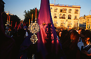 """Hermandad de Lansada, Seville, Andalusia, Spain...Semana Santa de Sevilla, Catholic Holy Week from Palm Sunday to Easter Sunday, is one of the most important traditional, cultural and spiritual events in Seville. The origins of the penitential Holy Week in Seville are to be found in the late Middle Ages. At the heart of Semana Santa are the brotherhoods (Hermandades y Cofradias de Penitencia).  At the centre of each procession are the pasos, an image or set of images set atop a movable float of wood. When a brotherhood has three pasos, the first one would be a sculpted scene of the Passion or an allegorical scene, known as a misterio (mystery); the second an image of Christ and the third an image of the Virgin Mary known as a dolorosa. Many sculptures are of great antiquity and considered artistic masterpieces. A total of 60 penitential processions are organized by hermandades and cofradías, religious brotherhoods. Members precede the pasos dressed in penitential robes and hoods. Sometimes accompanied by brass bands. They take designated routes from home churches and chapels to the Cathedral and back again. Improvised flamenco songs """"saetas"""" are sung to the processions from balconies. The marchers are often accompanied by brass bands, cappella choirs, or a drum and trumpet (historical traditions for a poorer neighborhood)"""
