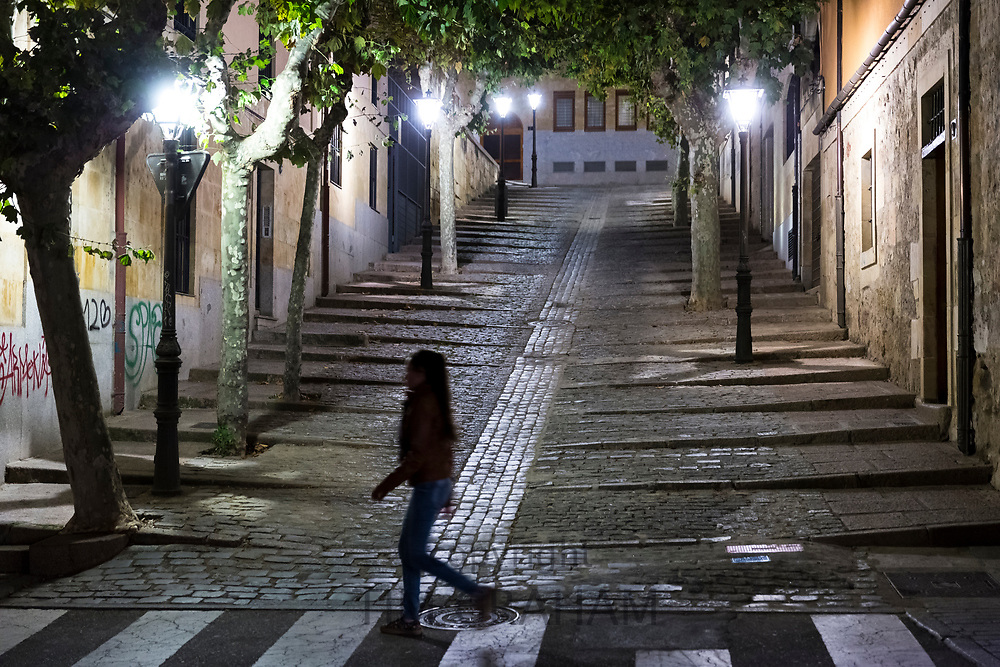 Stylish trendy young woman walking by Cuesta de Carvajal cobbled street in Salamanca, Spain