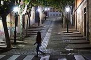 Stylish trendy young woman walking by Cuesta de Carvajal cobbled street in Salamanca, Spain