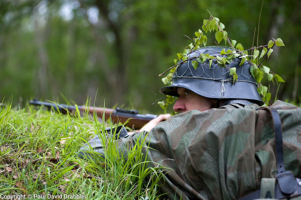 Reenactor from Northern World War Two Association, dressed as Panzer Grenadier from the Elite Grossdeutschland Division armed with a Mauser K98 and wearing the iconic coal scuttle helmet (stahlhelm) with splinter pattern camouflage zeltbahn  during a private 24hr exercise, held at Sutton Grange, near Ripon in Yorkshire. <br /> 15 May 2010 <br /> Images © Paul David Drabble.