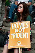 . A woman holds a placard saying 'Homes not trident'