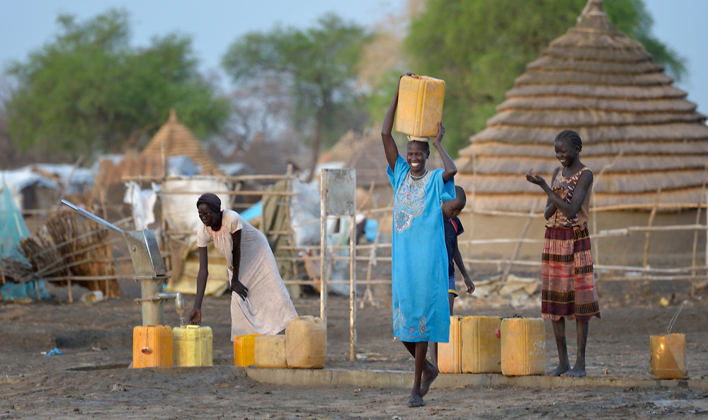 A woman carries home water from a well constructed by Caritas in a displaced persons camp in Agok, South Sudan. Tens of thousands of residents of Abyei, a contested region along the border between Sudan and South Sudan, remain displaced in Agok. Under a 2005 peace agreement, Abyei was supposed to have a referendum to decide which country it would join, but the two countries have yet to agree on who can vote. In 2011, militias aligned with Khartoum drove out most of Abyei's Dinka Ngok residents, pushing them across a river into the town of Agok. More than 40,000 Dinka Ngok have since returned to Abyei with support from Caritas South Sudan, which has drilled wells, built houses, opened clinics and provided seeds and tools for the returnees. Yet continuing insecurity means a greater number remain in Agok, where they remain dependant on Caritas and other organizations for food and other support.