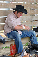 Austin Foss, from Terrebonne, Oregon begins taping up two hours before Friday night's events at the 2013 California Rodeo Salinas.