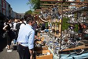 Silverware stall on Portobello Road Market in Notting Hill, West London, England, United Kingdom. People enjoying a sunny day out hanging out at the famous Sunday market, when the antique stalls line the street.  Portobello Market is the worlds largest antiques market with over 1,000 dealers selling every kind of antique and collectible. Visitors flock from all over the world to walk along one of Londons best loved streets.