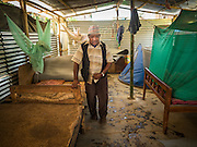 04 AUGUST 2015 - BUNGAMATI, NEPAL:   A man walks through the temporary structure he shares with eight other families in Bungamati, a village about an hour from Kathmandu. Three months after the earthquake many families still live in tents and temporary shelters scattered around the village. The Nepal Earthquake on April 25, 2015, (also known as the Gorkha earthquake) killed more than 9,000 people and injured more than 23,000. It had a magnitude of 7.8. The epicenter was east of the district of Lamjung, and its hypocenter was at a depth of approximately 15 km (9.3 mi). It was the worst natural disaster to strike Nepal since the 1934 Nepal–Bihar earthquake. The earthquake triggered an avalanche on Mount Everest, killing at least 19. The earthquake also set off an avalanche in the Langtang valley, where 250 people were reported missing. Hundreds of thousands of people were made homeless with entire villages flattened across many districts of the country. Centuries-old buildings were destroyed at UNESCO World Heritage sites in the Kathmandu Valley, including some at the Kathmandu Durbar Square, the Patan Durbar Squar, the Bhaktapur Durbar Square, the Changu Narayan Temple and the Swayambhunath Stupa. Geophysicists and other experts had warned for decades that Nepal was vulnerable to a deadly earthquake, particularly because of its geology, urbanization, and architecture.    PHOTO BY JACK KURTZ