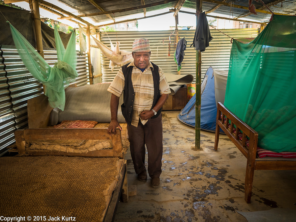 04 AUGUST 2015 - BUNGAMATI, NEPAL:   A man walks through the temporary structure he shares with eight other families in Bungamati, a village about an hour from Kathmandu. Three months after the earthquake many families still live in tents and temporary shelters scattered around the village. The Nepal Earthquake on April 25, 2015, (also known as the Gorkha earthquake) killed more than 9,000 people and injured more than 23,000. It had a magnitude of 7.8. The epicenter was east of the district of Lamjung, and its hypocenter was at a depth of approximately 15km (9.3mi). It was the worst natural disaster to strike Nepal since the 1934 Nepal–Bihar earthquake. The earthquake triggered an avalanche on Mount Everest, killing at least 19. The earthquake also set off an avalanche in the Langtang valley, where 250 people were reported missing. Hundreds of thousands of people were made homeless with entire villages flattened across many districts of the country. Centuries-old buildings were destroyed at UNESCO World Heritage sites in the Kathmandu Valley, including some at the Kathmandu Durbar Square, the Patan Durbar Squar, the Bhaktapur Durbar Square, the Changu Narayan Temple and the Swayambhunath Stupa. Geophysicists and other experts had warned for decades that Nepal was vulnerable to a deadly earthquake, particularly because of its geology, urbanization, and architecture.    PHOTO BY JACK KURTZ