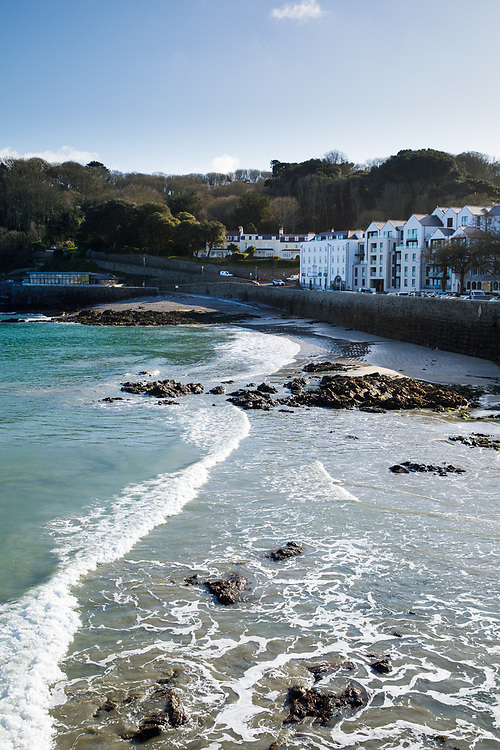 High tide at the beach in St Peter Port, Guernsey, CI, overlooked by apartments and flats with their beachfront locations