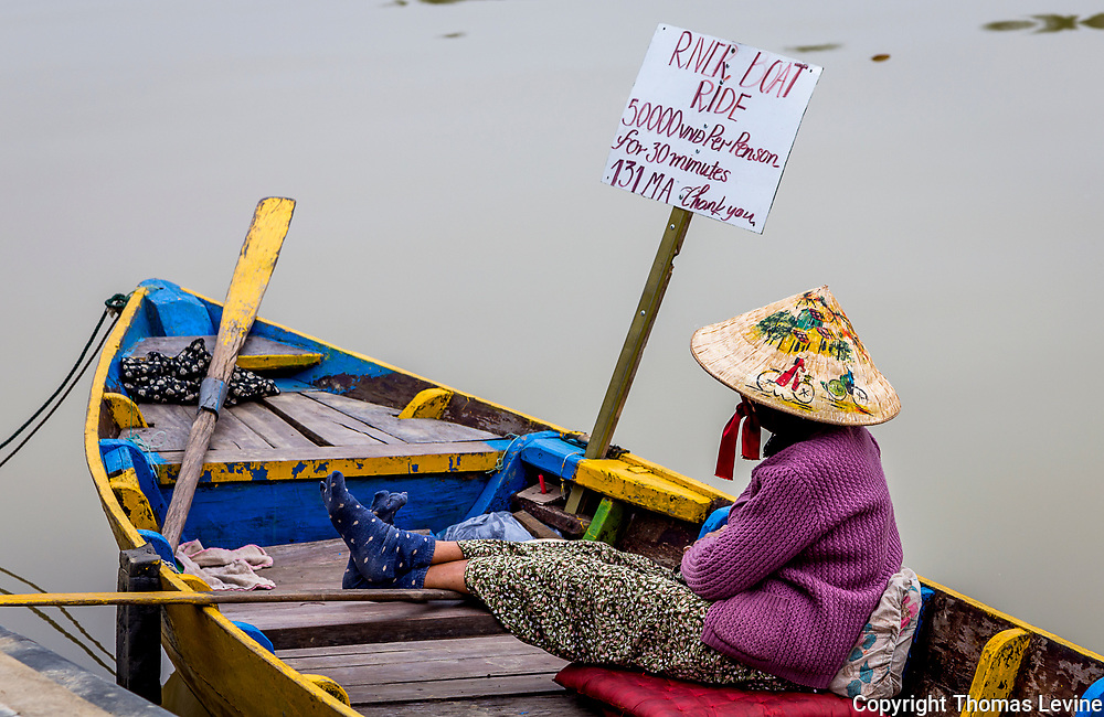 Dec,. 2017 Hoi an: Boat Rides on the Thu Bon River in Old Town, Hoi an, Vietnam.<br /> <br /> A Vietnamese Lady relaxes on her boat wearing her conical hat with bicycles on it.