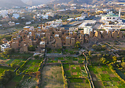 SAUDI ARABIA FROM ABOVE<br /> Vew of an old village with traditional mud houses and gardens on the outskirts of the southern city of Dhahran Al Janub. The architecture bears a similarity to the famous Yemeni city of Shibam, which is called the Manhattan of the Desert. Yemen is only 10 kilometers away. Dhahran Al Janub is not located in the desert but it also deserves such a nickname. The gardens remain well-kept and were used to offer a means of escape in case of tribal raids and defeat.
