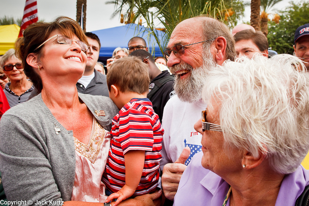 22 OCTOBER 2010 - PHOENIX, AZ:  SARAH PALIN and her son TRIG, talk to DON TURNBOUGH and his wife, PAT TURNBOUGH, at a Tea Party rally in Phoenix, AZ, Friday. About 300 people attended a Tea Party rally on the lawn of the Arizona State Capitol in Phoenix Friday. They demanded lower taxes, less government spending, repeal of the health care reform bill, and strengthening of the US side of the US - Mexican border. They listened to Arizona politicians and applauded wildly when former Alaska Governor Sarah Palin and her son, Trig, made a surprise appearance. The event was a part of the Tea Party Express bus tour that is crossing the United States.     Photo by Jack Kurtz