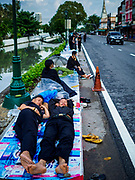 24 OCTOBER 2017 - BANGKOK, THAILAND: People sleep on the sidewalk along Atsadang Road while they wait to enter the royal cremation site. People started camping out along Atsadang Road in Bangkok near the royal cremation site on Monday. The gates won't open until Wednesday morning and the cremation isn't until Thursday night, so most people will sleep outside, on sidewalks and footpaths for three nights. Hundreds of thousands of people are expected to try to get into Sanam Luang, the site of the cremation of Bhumibol Adulyadej, the Late King of Thailand, but the site will only hold about 60,000 people. The Thai government has built replica crematoriums around Bangkok to accommodate the overflow crowds.        PHOTO BY JACK KURTZ