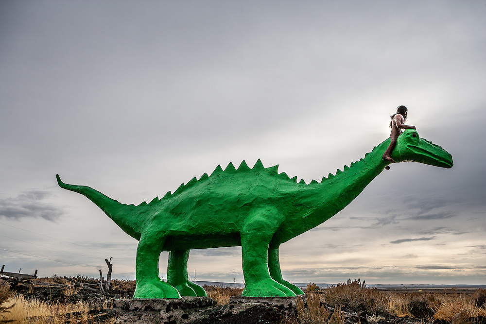 Tourist attraction along highway 75 north of Shoshone Idaho has underground Ice Caves and outside Dinosaurs. Ice Caves Prehistoric Man Rides Dinosaur through the volcanic desert of Southern Idaho.  Licensing and Open Edition Prints.