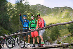 Three mountain biker friends standing on footbridge and showing something to his friends, Zillertal, Tyrol, Austria