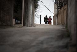 26 February 2020, Abu Dis, Palestine: Two women walk on a street near the Al-Quds ('Jerusalem') University in Abu Dis.