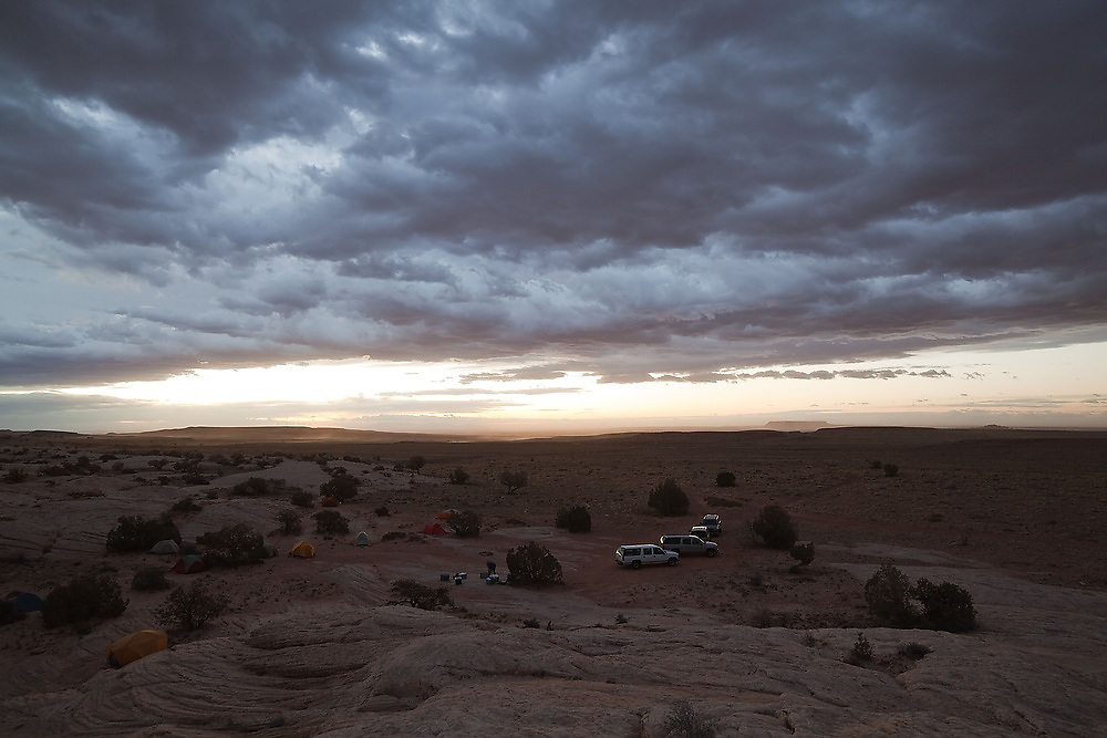 Storm clouds pass over a group campsite at sunrise near the San Rafael Swell, Utah.
