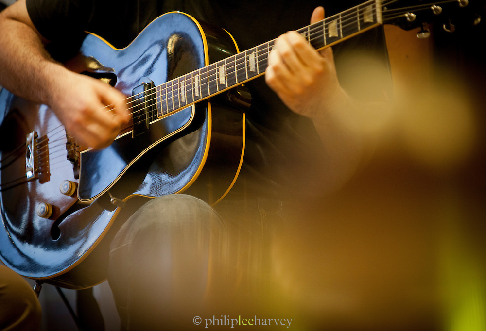 A guitarist strumming at a live music event at a bistro in the centre of Paris, France