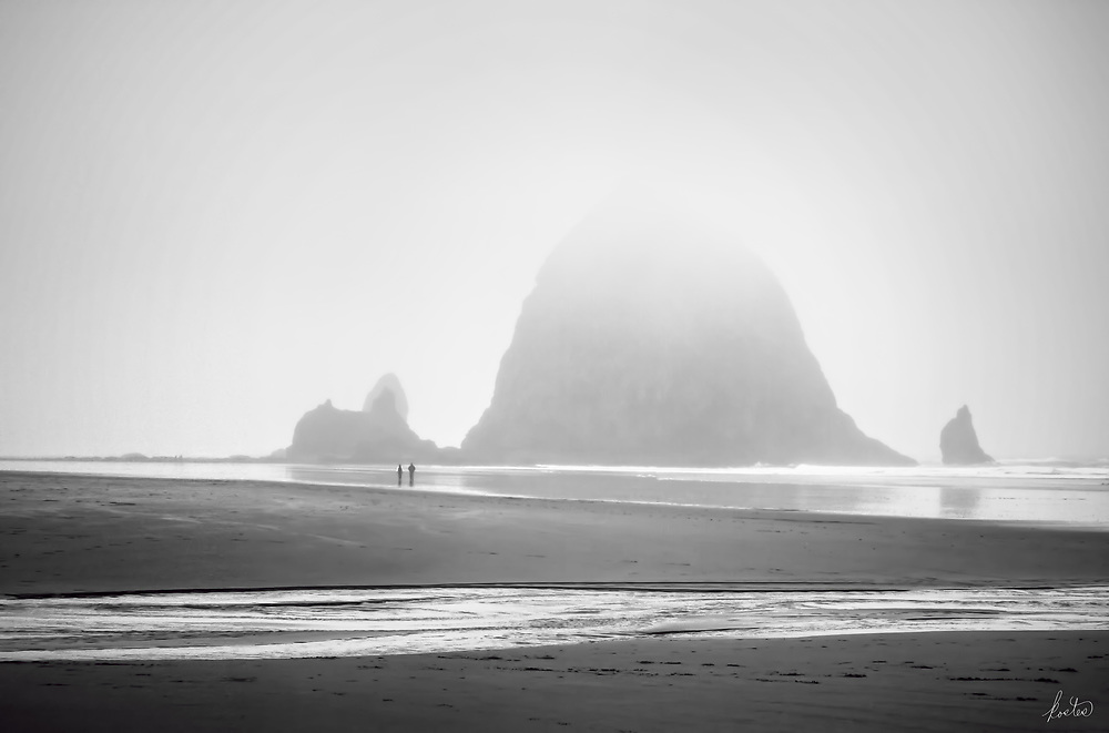 Haystack Rock in Cannon Beach is shrouded in fog, in fact the top is completly hidden. A couple is out walking in the fog, perfect for a black and white image.