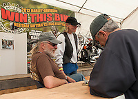 Keith and Lilo Hall man the Laconia Rotary Booth on Lakeside Avenue as Steve Vanni purchases his chance to win the Harley Davidson Heritage Softtail Classic which will drawn on Sunday.  (Karen Bobotas/for the Laconia Daily Sun)