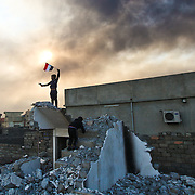 Neighborhood children play around homes reduced to rubble in Qayyarah, a town near oil fields which ISIL set ablaze while under retreat at the start of the Mosul offensive which began more than a month prior.