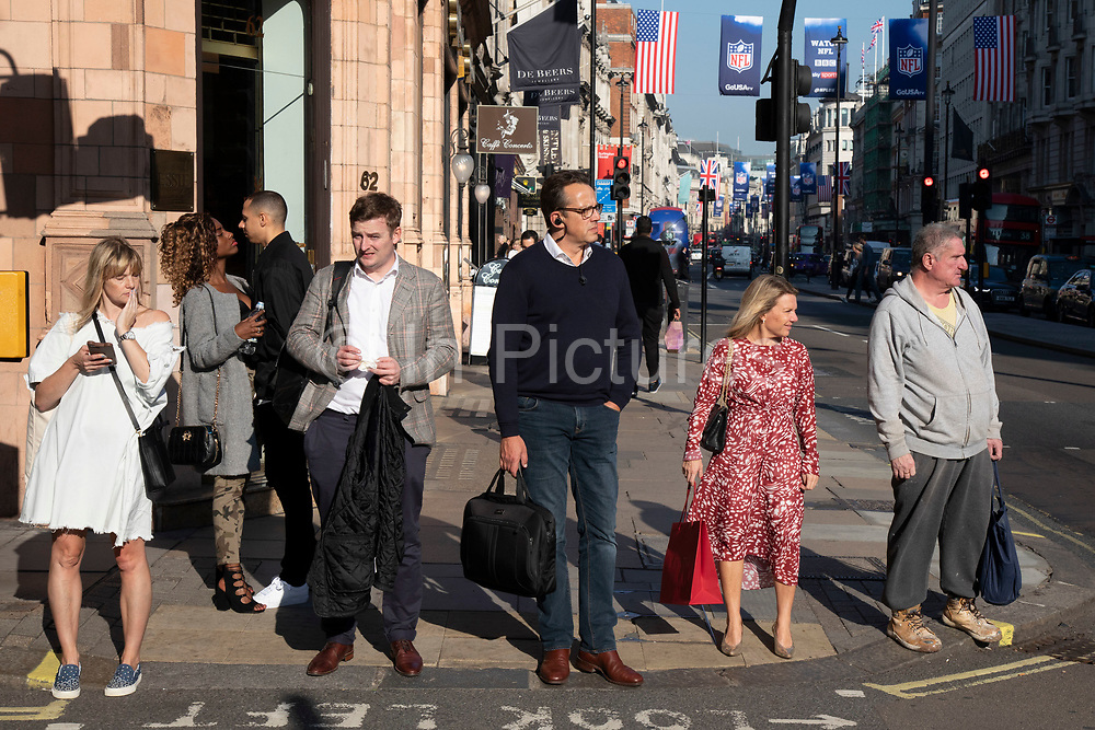 People of different characters and backgrounds all waiting at the same junction to cross the road on Piccadilly in London, United Kingdom.